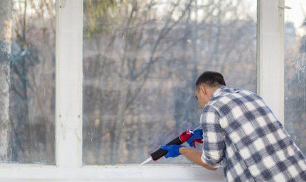 mezczyzna kladzie silikon na okna