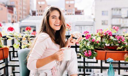 kobieta wsrod kwiatow na balkonie
